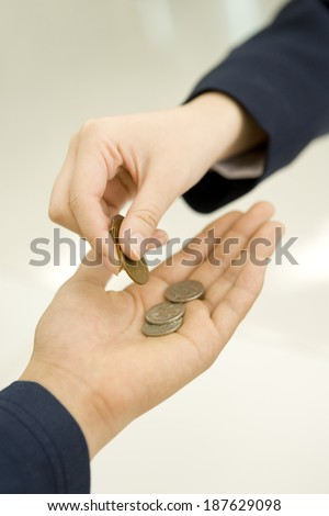 Hand paying coins into the palm of another person's hand.