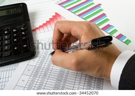 Hand, pen and calculator on the financial papers