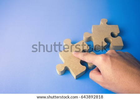 hand pick the wooden jigsaw puzzle in business plan concept