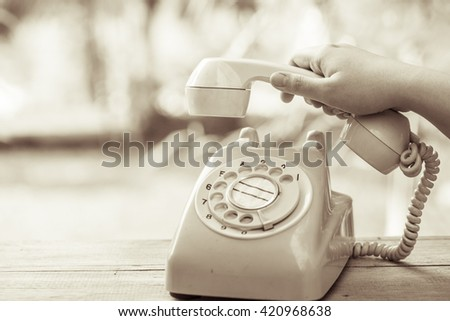 hand pick up old day phone or rotary telephone on wood table vintage color tone - stock photo