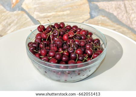 Hand picked cherries in bowl on brick countertop