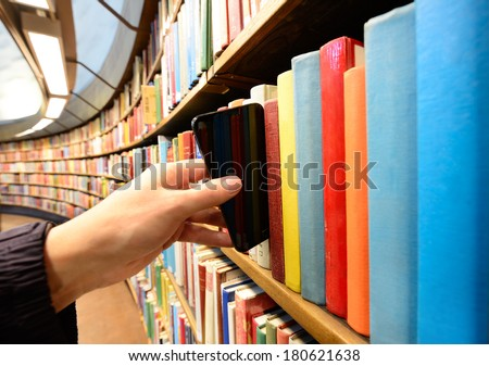Hand picking a tablet computer out of bookshelf in library - stock photo