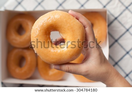 Hand picking donuts over the box - stock photo