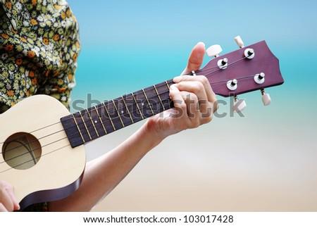 hand picking Guitar ,Ukulele on the beach. - stock photo