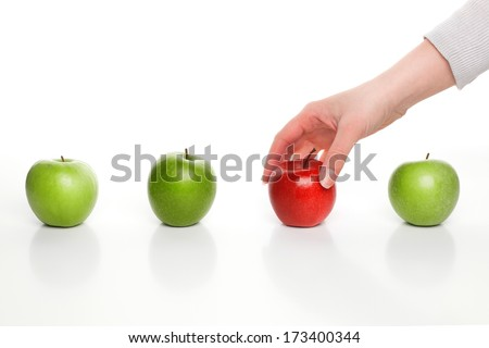 Hand picking red apple among green apples - stock photo