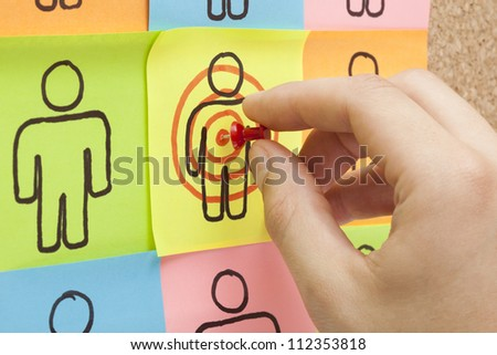 Hand pinning a sticky note in the center of a customer target on cork board - stock photo