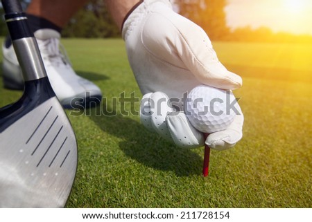 hand placing a tee with golf ball - stock photo