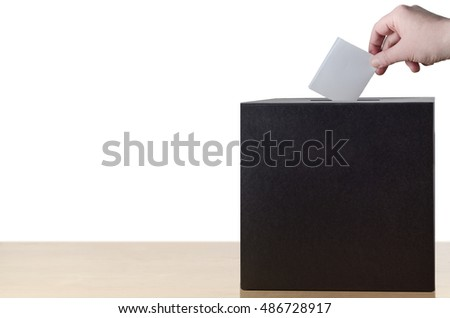 Hand placing folded voting slip into slot in ballot or suggestion box on light wood table.  Isolated on white background.
