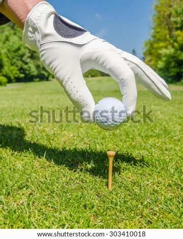 hand placing golf ball on tee over beautiful golf course with blue sky - stock photo