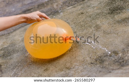 hand play yellow water balloon at outdoor on floor