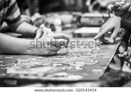 Hand playing board game, strategy concept. black and white filter - stock photo
