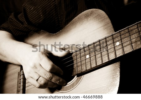 hand playing guitar at black background - stock photo