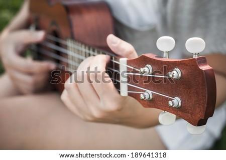 Hand playing guitar or ukulele - stock photo