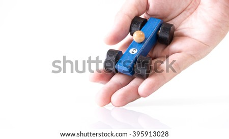 Hand playing with blue wooden toy race car on white empty background. Concept of dream car ownership and financing. Slightly de-focused and close-up shot. Copy space.