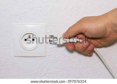 Hand plugs electrical cord in white wall socket
