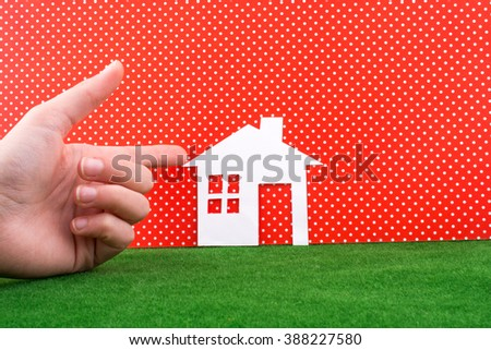 Hand pointing a Paper house on a white-dotted red background with grass