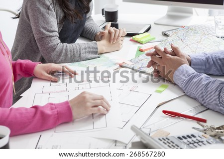 Hand pointing architectural blueprint. over blurred architectural blueprint of office building
