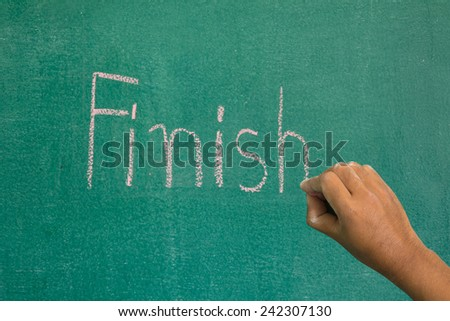 Hand pointing at finish word of success concept on chalkboard - stock photo