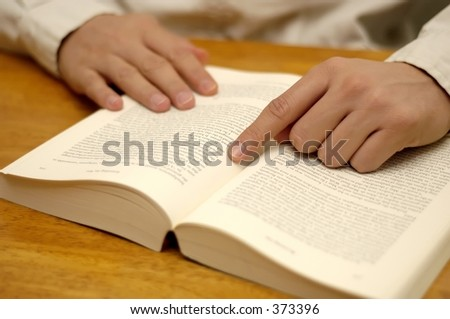Hand pointing at page on a book. Shallow depth of field, focus on hand. - stock photo