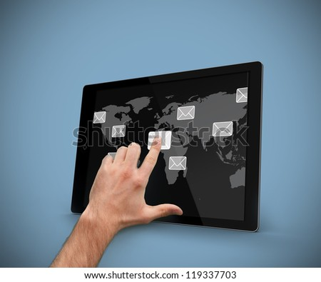 Hand pointing at tablet computer with email symbols and world map backdrop against blue background