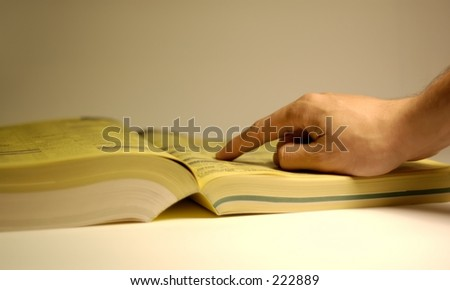 Hand pointing at yellow page ad. Shallow depth of field, focus on hand. - stock photo
