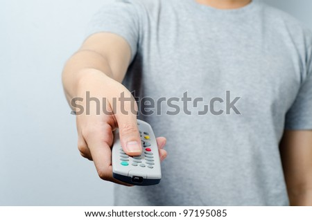Hand pointing remote control in front - stock photo