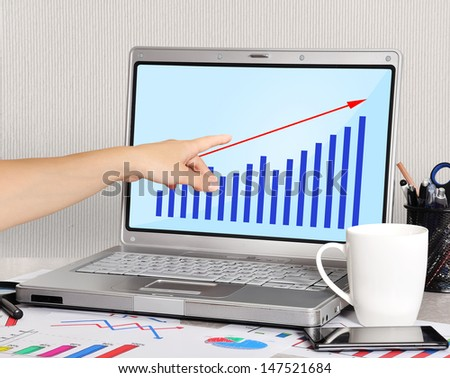 hand pointing to chart screen laptop - stock photo
