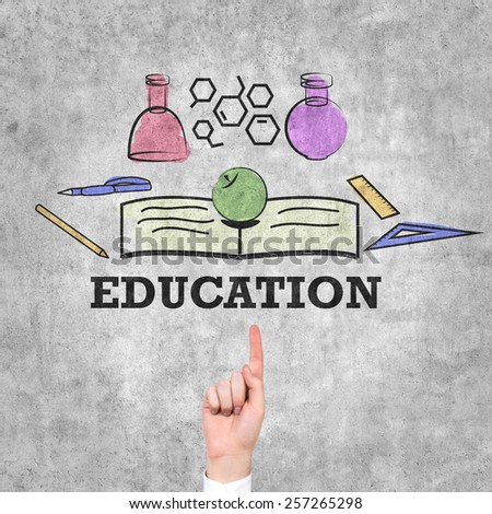 hand pointing to education symbol on wall - stock photo