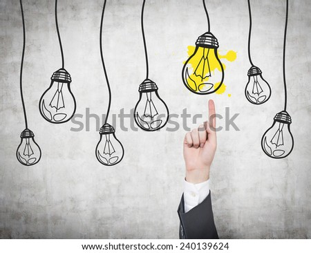 hand pointing to many lightbulb on gray background - stock photo