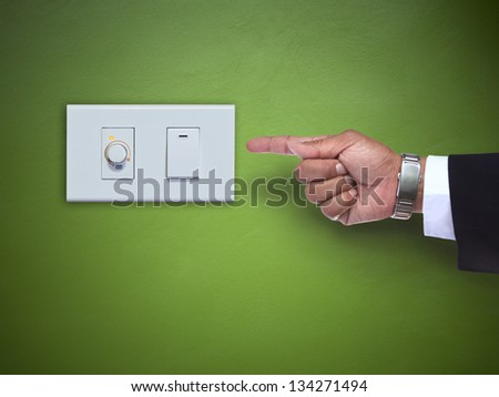 hand pointing to switch of electric appliance on green wall use for multipurpose - stock photo