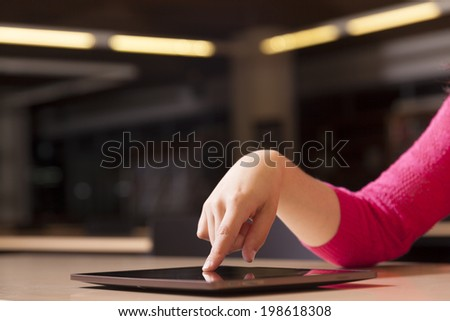Hand pointing to tablet computer in library - stock photo