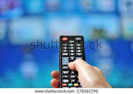 Hand pointing tv remote control and tv set - stock photo