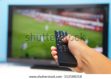 Hand pointing tv remote control towards the television as background  - stock photo