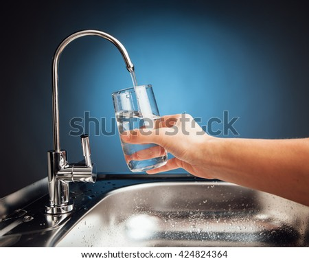 hand pouring a glass of water from filter tap, blue background - stock photo