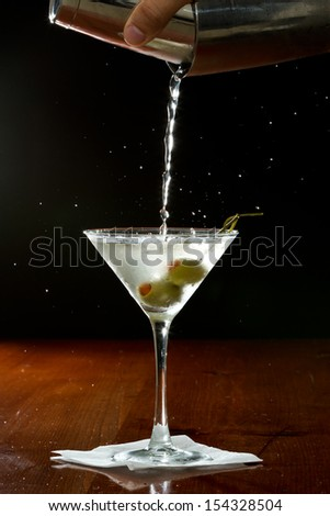 hand pouring a martini into  a chilled glass over a black background - stock photo