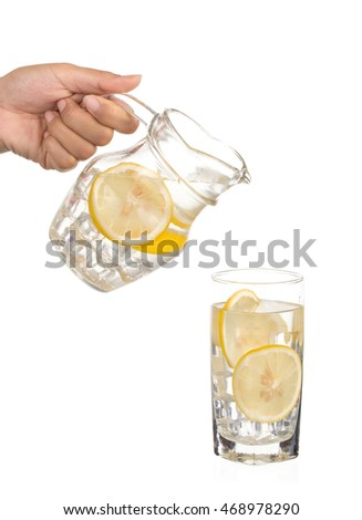 Hand pouring lemonade from jug with ice into glass isolated on white background