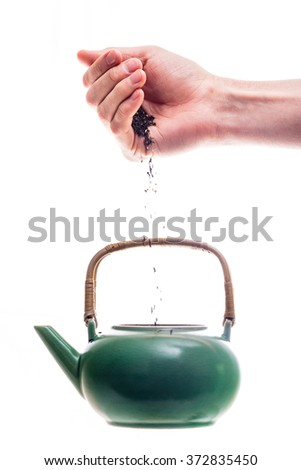 Hand pouring tea leaves into the green ceramic teapot