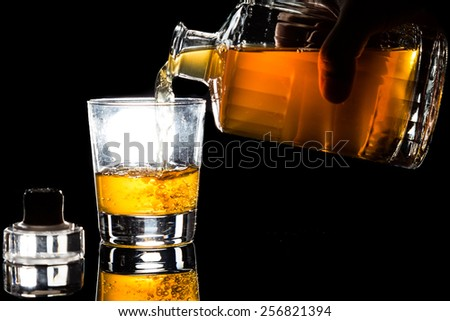 Hand pouring whiskey into a glass within a dark background - stock photo