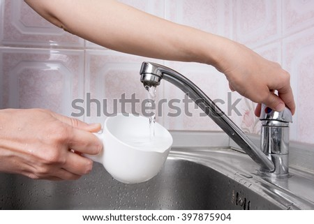 hand pours water into a cup