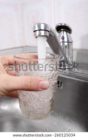 hand pours water into a glass from kitchen faucet - stock photo