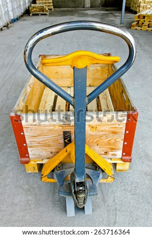 Hand powered pallet jack handle control in warehouse - stock photo