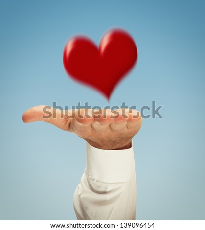 Hand presenting heart with motion blur on clear blue sky - stock photo