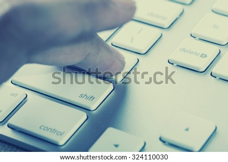 Hand press ENTER to computer keyboard. Retro filter - stock photo