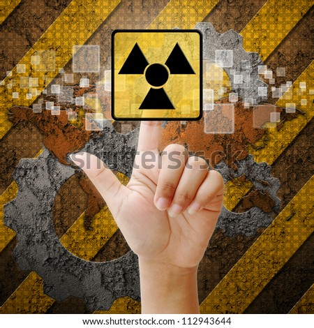 Hand press touch Nuclear symbol on industry background