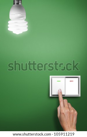 hand pressed to switch to turn on the light with green background