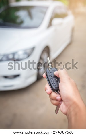 hand presses on the remote control car alarm systems - stock photo