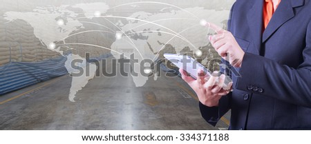 hand presses on world map with digital tablet,export and import goods prepare the delivery of raw material in warehouse background (Elements of this image furnished by NASA) - stock photo