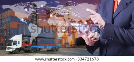 hand presses on world map with digital tablet,Industrial Container Cargo freight ship  in shipyard at dusk for Logistic Import Export background (Elements of this image furnished by NASA) - stock photo