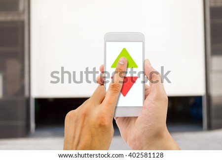 hand pressing a remote control with smartphone - stock photo