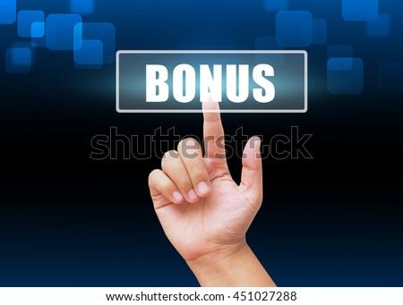 Hand pressing BONUS button on technology background  - stock photo